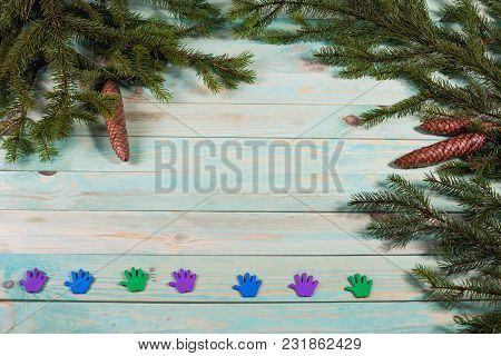 Christmas Background With Spruce Branches With Colored Traces Of Palms On Wooden Board With Copy Spa
