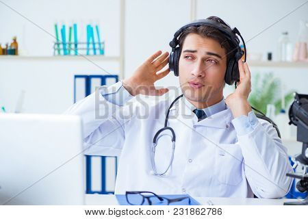Happy excited doctor listening to music during lunch break in hospital