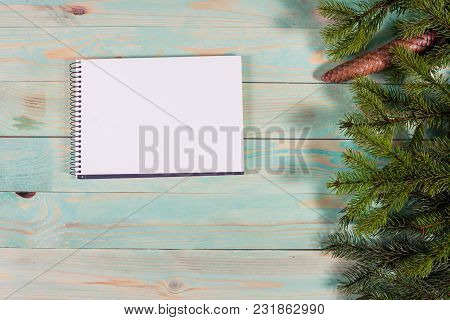 Christmas Background With Spruce Branches On Wooden Board With Notebook Copy Space