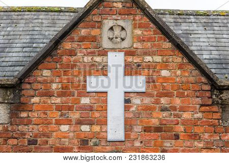 Day Viev Of White Cross On Church Brick Wall In England.