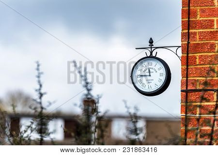 English Brick House Corner With Dangling Retro Clock With Paddington Station London Text On It.