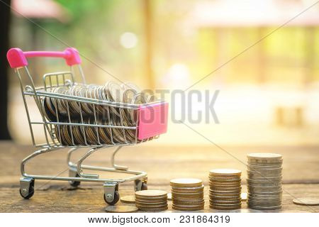 Saving Money Concept With Money On Cart And Coin Stack Growing Business On Abstract Sunset Backgroun
