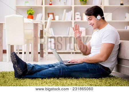 Man working on laptop at home on carpet floor