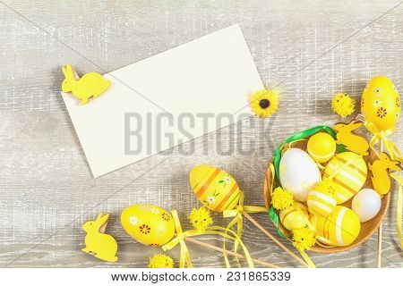 Composition With Painted Eggs And Other Easter Attributes And Accessories In Yellow Tones On A Light
