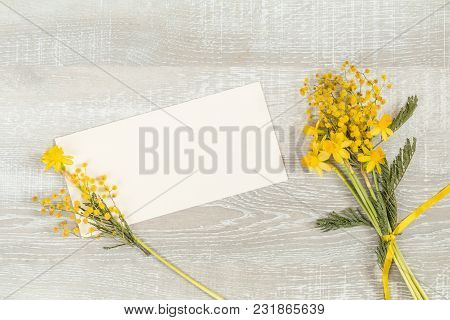 Mimosa And Yellow Daffodils On A Light Wooden Surface. Yellow Orange Flowers Concept, Top View, Copy