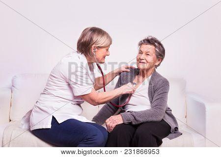 Studio Portrait Of A Senior Nurse Examining An Elderly Woman With A Stethoscope.