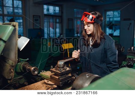 Young Woman Student Works On An Automatic Lathe Cnc, Industrial Workshop. Concept Vocational Educati