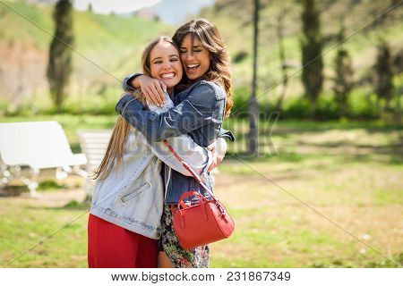 Two Happy Young Women Friends Hugging In Urban Park.