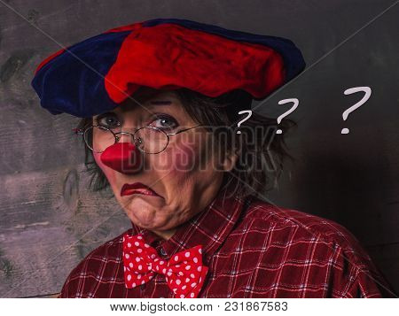 Face Of Doubting Clown In Red Beret And With Three Question Marks In His Head On A Dark Wooden Backg