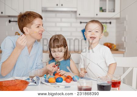 Preparation For Easter. Mom And Children Paint Eggs With Paints And Brushes. Fun And Laugh. Concept