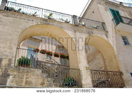 Typical White Houses And Two Arches  With Red Flowers And Plants In Polignano A Mare