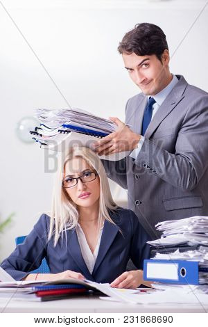 Boss bringing additional work to his assistant secretary