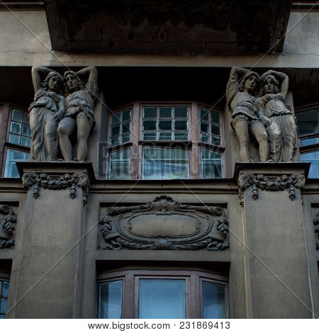 Sculpture On The Facade. A Man And Woman Together Carry  Large Load.