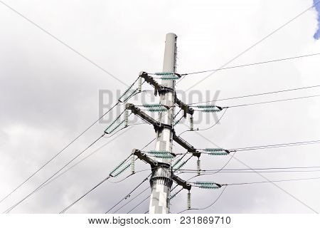 High Voltage Power Lines And Large Pylon Above Grey Sky
