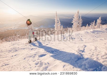 Young Woman On Snowboard Sits On Snow And Waits For An Instructor To Skate Freely On Fresh Snow. She