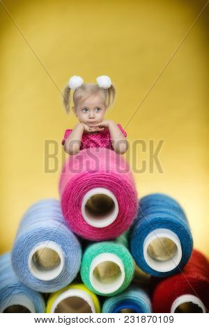 A Beautiful Blonde Girl Laid Her Head On Her Hands Next To A Bunch Of Huge Reels With Sewing Threads