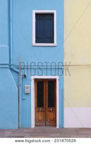 Retro Vertical Blue Facade With Closed Entrance Wooden Door