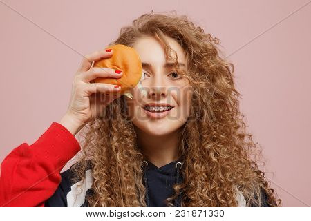 Girl With Braces On Her Teeth Bites Burger, Curly Hair, Pink Background. Concept Rejection Of Fast F