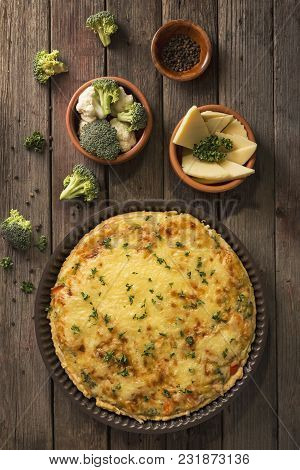 Table Top Shot Of A Fresh Vegetarian Pie Served On A Cutting Board On Rustic Wooden Table