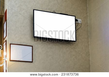 Televisor On A Wall With A Blank Frame For Your Advertising