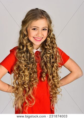 Happy Girl In Red Dress On Grey Background. Beauty, Kid Fashion, Cosmetics, Healthy Hair. Hair Salon