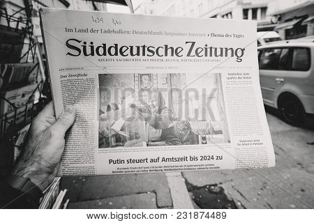 Paris, France - Mar 19, 2017: Man Reading Buying German Sudeutsche Zeitung Newspaper At Press Kiosk