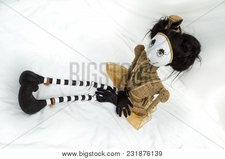 Creepy Steampunk Rag Doll Sitting With Legs Outstretched. High Angle View. Lifesize Doll On A Grungy