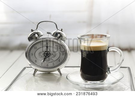 Morning. Alarm Clock With Cup Of Coffee And White Background Selective Focus