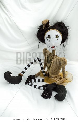 Creepy Steampunk Rag Doll Sitting With Legs Bent. Looking Forward. Lifesize Doll On A Grungy White B