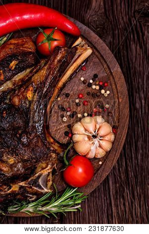 Top View Delicious Grilled Beefsteak With Peppercorn, Garlic, Tomato And Pepper On Dark Wooden Backg