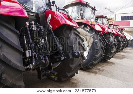 Red Parked Tractor, Stand In A Row, A Photo From Behind