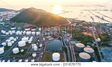 Aerial View Oil Refinery With A Background Of Mountains And Sky.