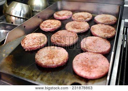 Rows Of Burger Patties Cooking On A Hot Griddle