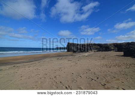 Pretty Coastal Shore With Blue Skies And Wet Sand