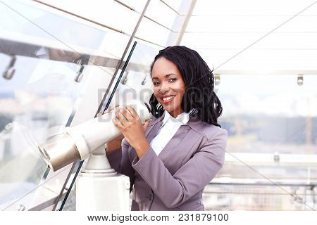 Portrait Of A Happy Businesswoman Looking Through Binoculars Against Cityscape
