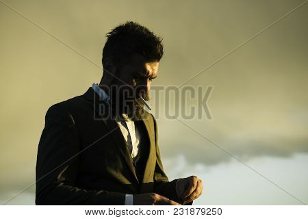 Man With Beard And Cigarette With Dramatic Sky On Background. Hipster With Stylish Appearance Smoke