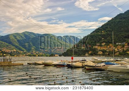 Row Of Boats On Lake Como With Mountains In Background, Italy