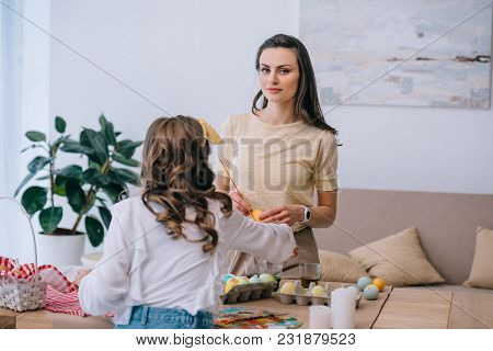 Young Mother And Daughter Painting Easter Eggs At Home