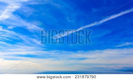 A Deep Blue Sky With White Clouds And Blue Sea, On The Horizon You Can See The Mountains