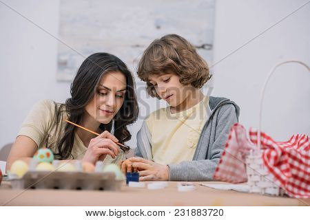 Young Mother And Son Painting Easter Eggs Together At Home