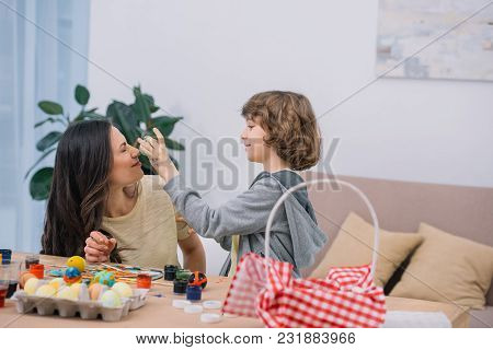 Son Playing With Mother While Preparing Easter Eggs