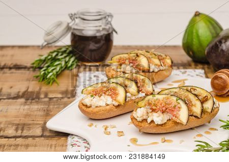 Swedish Toasts With Figs, Cheese, Rosemary, Honey And Walnuts On A Cutting Board