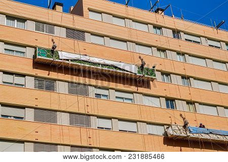 Malaga, Spain - February 23, 2018. Workers On The Exterior Scaffold Elevator To Repair The Building
