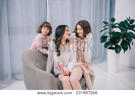 Kids Sitting On Cozy Armchair With Mother On Mothers Day