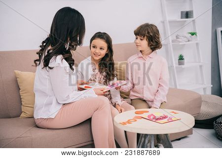 Children Presenting Mothers Day Greeting Cards To Mother