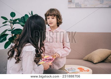 Son Presenting Greeting Card To Mother On Mothers Day