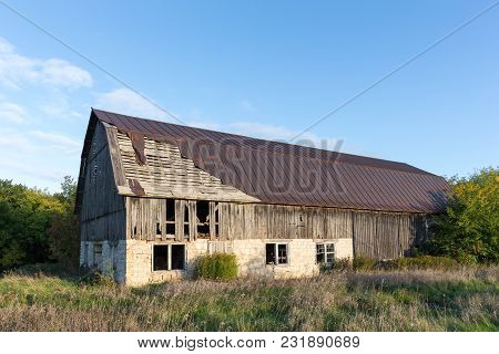 Abandoned And Dilapidated Barn Set Against A Blue Sky.  Concepts Could Include Rural Culture, Family