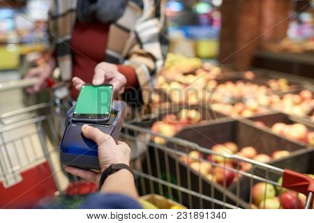 Close Up Modern Senior  Woman Buying Groceries In Supermarket Paying With Nfc Payment Via Smartphone