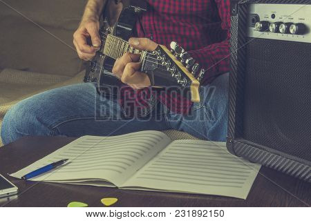 Hipster Musician Sits On The Couch And Plays The Electric Guitar. Before Him The Notes And A Guitar
