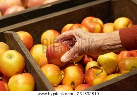 Close Up Of Wrinkled Hand Taking Ripe Golden Apples From Fruit Box In Supermarket Or Grocery Store,